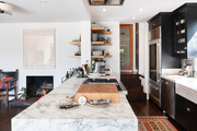 This kitchen features a marble island.