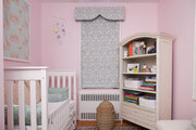 A framed piece of wallpaper and a pelmet box window treatment dress the pink walls of a girl's nursery
