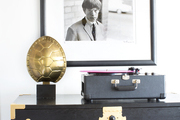 A record player and tortoiseshell lamp atop a wood console