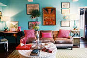 A brown couch and a round white coffee table in a blue living space
