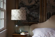 A bedside table with a glass lamp