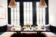 A built-in banquette and a pair of light fixtures in a breakfast nook