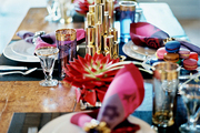 A colorful place setting with a gold candelabra and vintage glassware