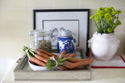 A mirrored tray topped with canisters and a bowl of carrots on a white table