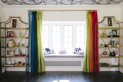 A colorful window seat in the living area is bookended by two bookcases.