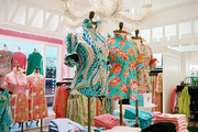 Lilly Pulitzer clothing on display below a white chandelier
