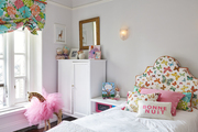 Colorful and bright children's room with  patterned headboard and white chest.