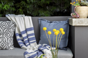 A midcentury tray topped with flower arrangements in front of an upholstered outdoor banquette