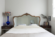 A glass lamp beside a bed with mirrored headboard in a white-painted room