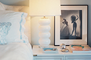 A white campaign chest with a white lamp beside a tufted headboard