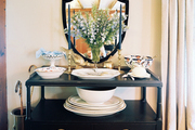 A shield-shaped mirror above a black sideboard covered with serving platters