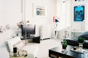 A white midcentury chair paired with a circular brass side table in a studio apartment
