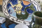 A decorative painted plate of a mermaid.