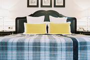Plaid bedding and bright yellow pillows in a white-walled bedroom