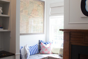 A framed map hung above a corner window seat