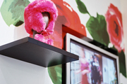 Black shelving and a TV on floral wallpaper