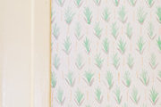 A detail of green and white leaf wallpaper.