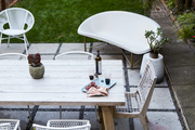 A modern patio with white and neutral furniture.