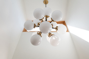 This modern light fixture features multiple round bulbs.