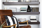 A handsome leather chair by DwellStudio cozies up to a built-in bookshelf in the master bedroom.