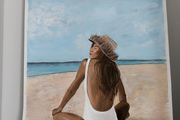 A detail of a painting of a girl at the beach.