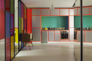 A colorful stained-glass wall treatment in the neon kitchen of designer Manish Arora's Paris apartment