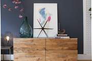 Wood dresser topped with art and decor