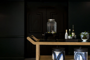Small wooden bar cart in contemporary room.