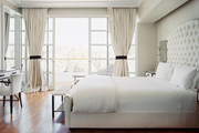 A guest room filled with white furniture and linens