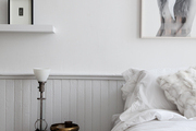White-painted beadboard and wall with framed artwork in a bedroom