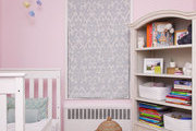 A pelmet box window treatment, wooden bookcase, and hand-knotted area rug in a nursery
