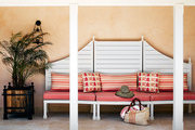 Stripes and ikat-print throw pillows on a sculptural upholstered bench