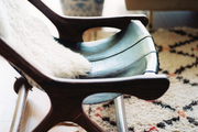 A midcentury chair placed atop a Beni Ourain carpet