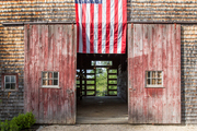 A rustic barn with a hanging American flag.