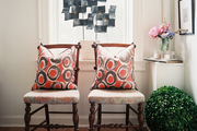 A pair of side chairs beside a boxwood ball