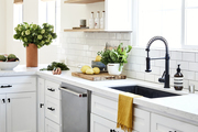 An all-white kitchen with black hardware.