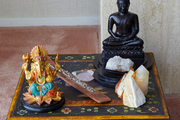 A Buddah statue and a Ganesh statue sit on  a painted accent table.
