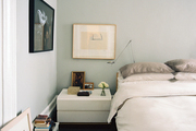 A bed dressed in neutral linens next to a minimalist white bedside table