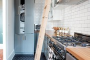 A contemporary kitchen with white subway tile and blue cabinets.