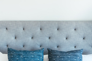 A tufted gray headboard in a contemporary bedroom.