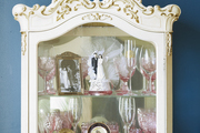 Glassware and a wedding cake topper displayed in an ornate glass cabinet.