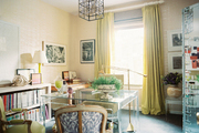 Green curtains and chairs with a Lucite desk in an office space