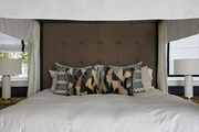 Patterned pillows atop white bedding and tall padded headboard.