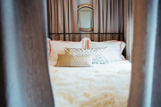 A round mirror at the head of a four-poster bed with linen curtains