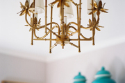 A vintage gold chandelier with white shades