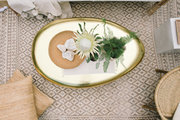 An overhead view of a gold coffee table on a neutral rug with neutral furniture.