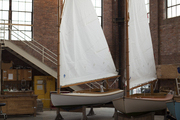Sailboats on display in a brick building