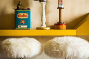 A trio of found objects stacked as sculptures above two sheepskin-covered stools