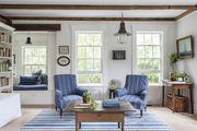Exposed beams on the ceiling of a living room dressed with blue-and-white striped textiles