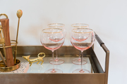 A detail of pink glasses on a contemporary bar cart.